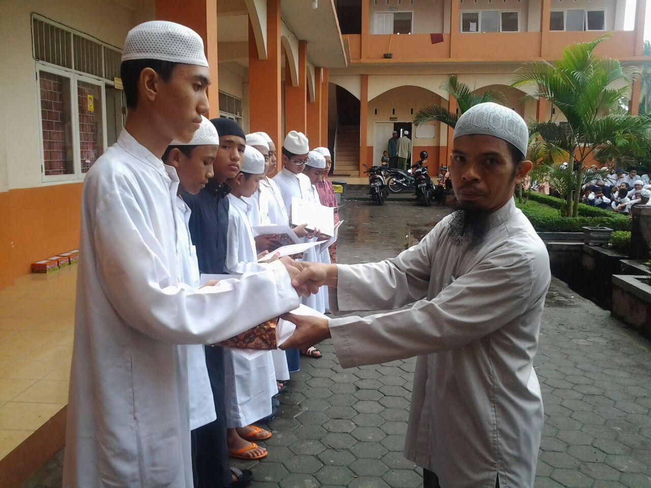 Kepala SMP IA, Pak Ahmad Yani tengah menyerahkan piagam penghargaan untuk santri berprestasi